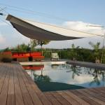 Das aufrollbare Sonnensegel rollt sich automatisch auf und zu. Terrasse und Pool in Arwangen.