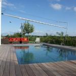 Beschattungssystem mit rollbarem Sonnensegel über Terrasse und Pool in Arwangen.