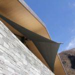 Steinfassade und Sonnensegel hellgrau