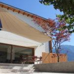 Aufrollbares Sonnensegel am modern renovierten Einfamilienhaus