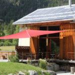 Bündnerhaus mit Sonnensegel über der Holzterrasse